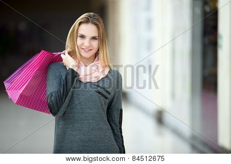 Cheerful Young Woman With Paper Bags In Shopping Center