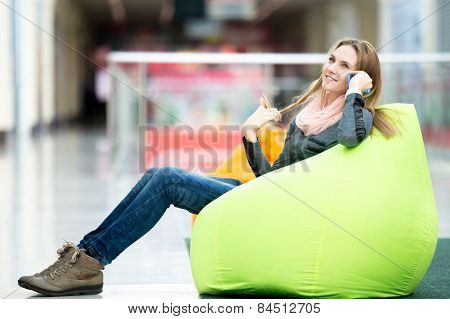 Smiling Female Sitting In Bean Bag In Office Or Shopping Center Talking On Mobile Phone