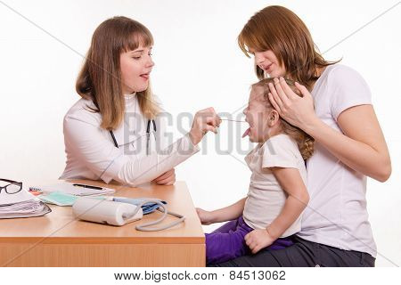 The Doctor Examines The Throat Of A Child Sitting On Hands Of Mother