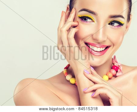 Girl model with bright make-up and coloured nail