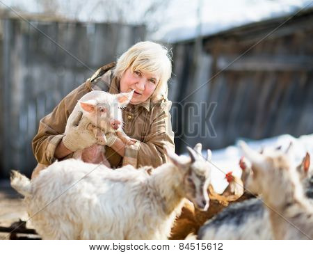 female farmer holding a small pig
