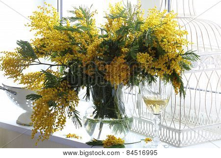 Bouquet Of A Mimosa And Wine Glass At A Window