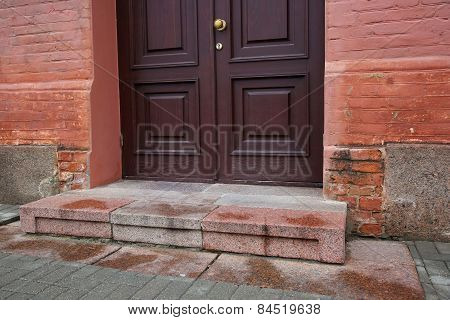 Porch With Dark Door Of Red Bricked Building