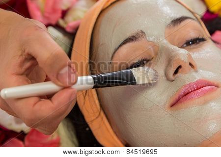 Beautician apply cream on the girl's face