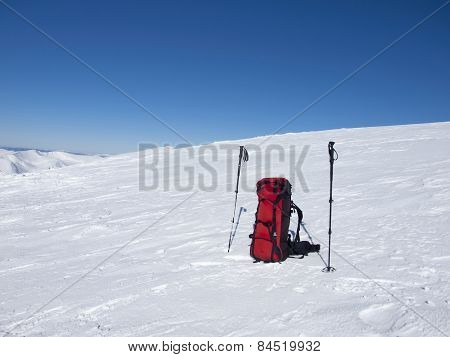 Backpack And Trekking Poles In The Snow.