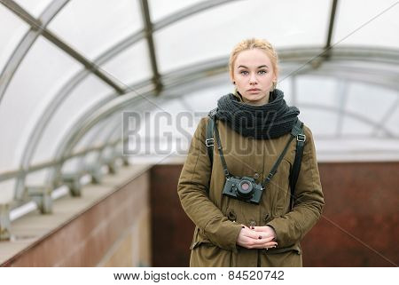 Outdoors city portrait of young blonde hipster woman photographer