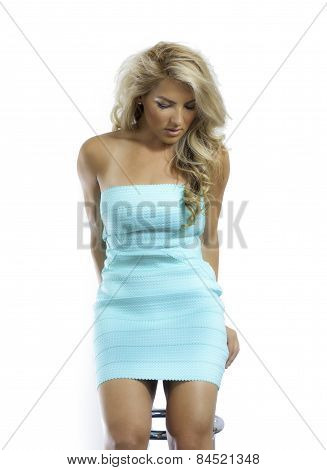 Blonde Latina Girl Blue Green Dress Sitting Stool