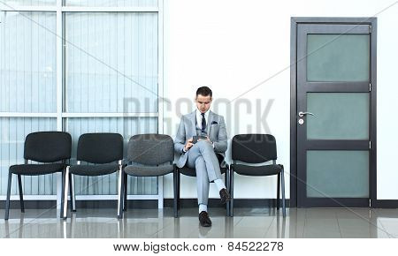 Ready for interview. Thoughtful man in formalwear holding paper while sitting at the chair in waitin