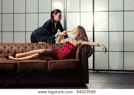 Beautiful Lesbian Flirting Couple On The Sofa.