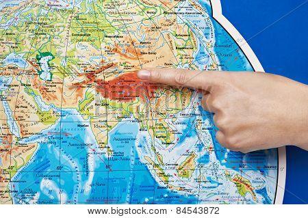 Hand Indicates Location On World Map.