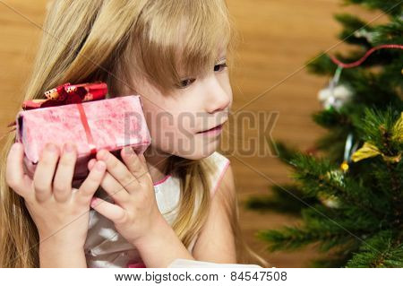 Girl with a gift in the Christmas tree.