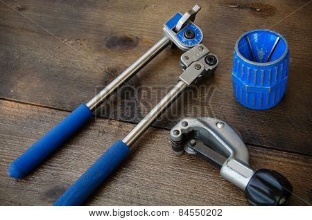 Tube bender or pipe bender tools on wooden background.