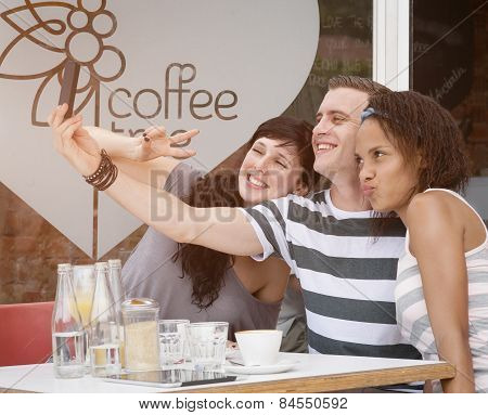 Group of young diverse individuals at coffee shop taking a selfie with smartphone