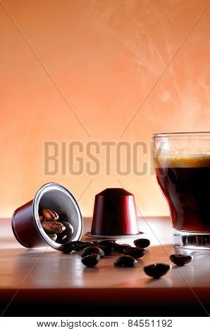 Capsules And Cup Of Hot Espresso Coffee Close Up