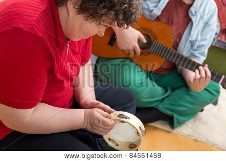 Mentally Disabled Woman Playing A Tamborin