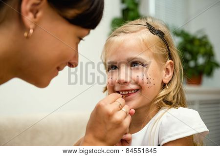 Woman paints the face of a child for the holiday
