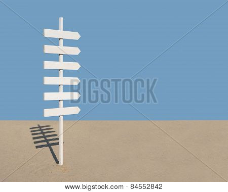 White wooden rustic sign post with six arrows on blue and beach sand