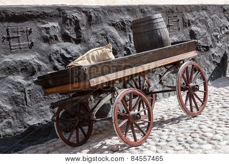 old wooden cart on background of brick wall