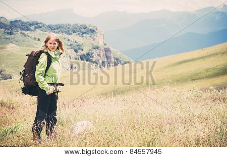 Woman Traveler hiking in Mountains with beautiful summer landscape on background