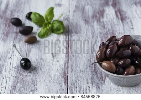 Pickled black olives in a bowl on wooden background.