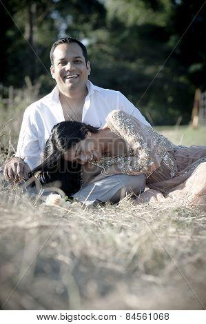 Beautiful young Indian couple relaxing outdoors in long grass