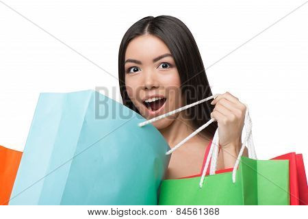Close up of asian surprised woman after shopping with bags
