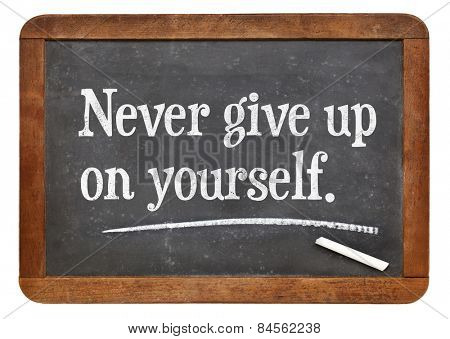 Never give up on yourself - motivational advice on a vintage slate blackboard