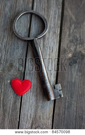 Big Key And Red Heart On Wooden Rustic Table
