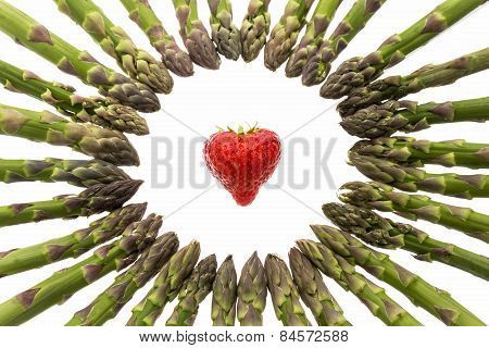 Circle Of Asparagus Tips Pointing At Strawberry.