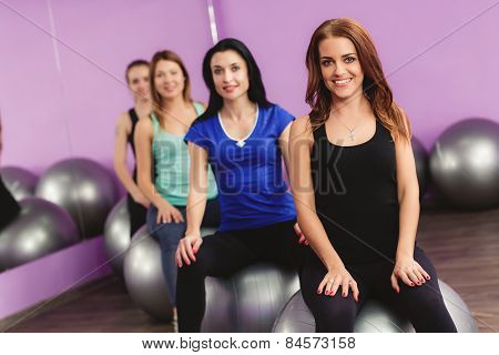 The girls are preparing to perform a set of exercises with a large ball for fitness.