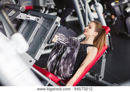 Young girl - gymnast performs exercises for legs on the machine - leg press.