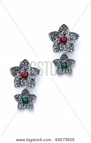 Silver Earrings In The Shape Of Flowers On A White Background
