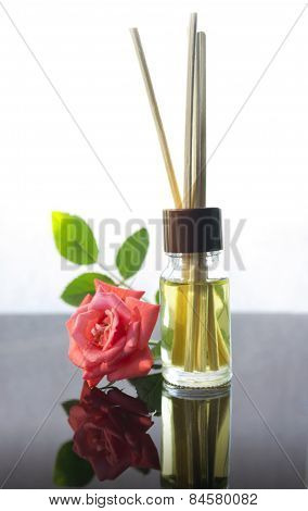 Rose scented oil bottle with wooden sticks on white