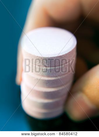 Hand holding a stack of effervescent tablets