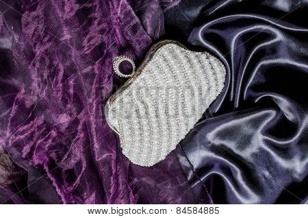 Clutch With Pearls On A Silk Background