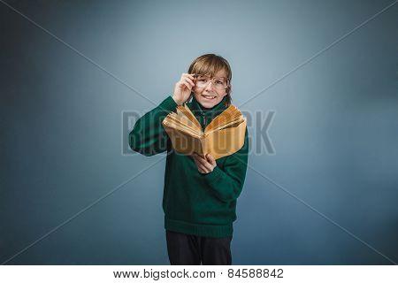 European-looking boy of ten years in glasses reading a book, smi