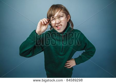 European-looking boy of ten years in glasses squints on a gray b