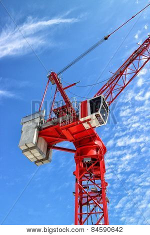 Top of red construction crane against blue sky