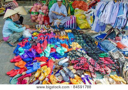 Colorful sandals and shoes for sale at an outdoor market in Vietnam