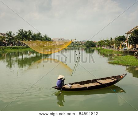 Vietnamese woman paddles a traditional boat on the Thu Bòn River