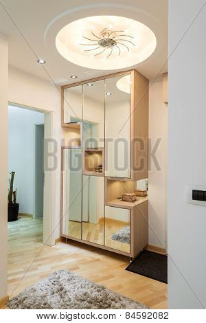 Elegance anteroom interior in warm tones with wardrobe and mirror