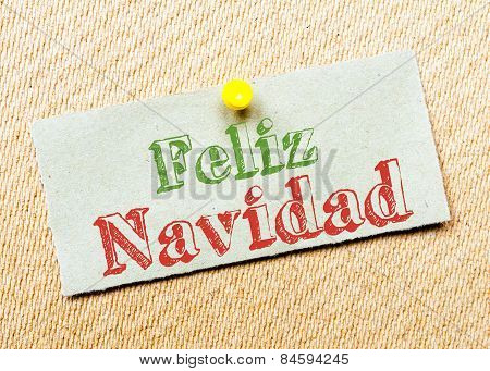 Recycled Paper Note Pinned On Cork Board. Feliz Navidad Message