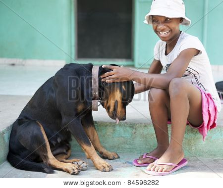 A tween Haitian girl happily petting a large black dog.