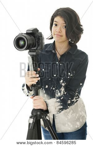 An attractive young teen looking at the viewer as she holds onto the tripod that supports her pro camera.  On a white background.