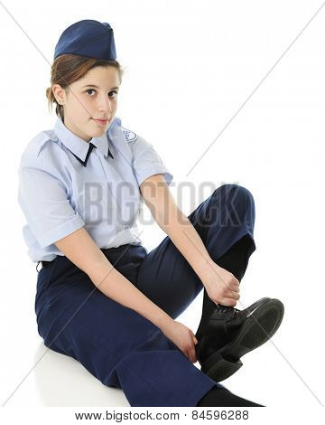 An attractive teen girl in her Jr. ROTC uniform, putting on her shoes.  On a white background.