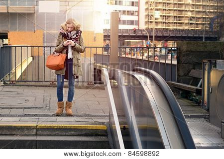 Young Woman Standing In Town Looking At Her Mobile