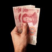 picture of yuan  - Modern Chinese 100 yuan renminbi banknotes in male hand isolated on black - JPG