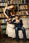 foto of shot glasses  - Young man in glasses is reading a book next to a sexy girl in lingerie in the library - JPG