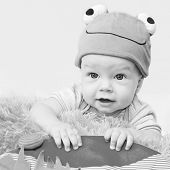 stock photo of cute frog  - cute baby playing in the hat frog lying on his stomach on a white background  - JPG