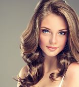 foto of brown-haired  - Smiling Beautiful girl brown  curly  hair with an elegant hairstyle - JPG